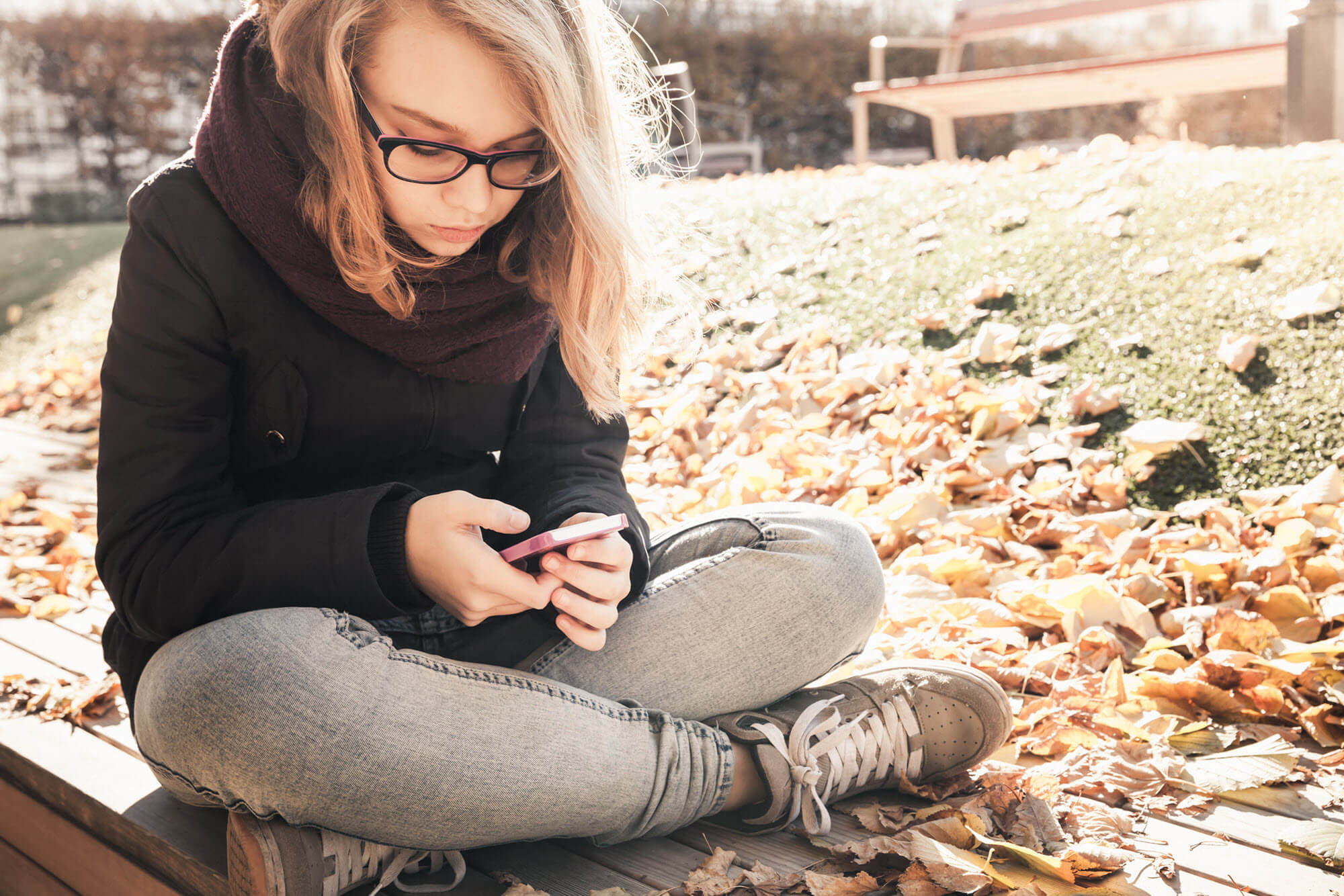 Girl in park sends message on her phone. Model photo.
